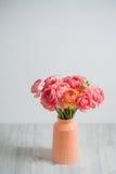 Bos van bleek - roze ranunculus Perzische boterbloemen lichte achtergrond, houten oppervlakte De vaas van het glas royalty-vrije stock foto's