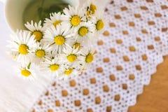 Bos van bloeiende madeliefjes op rustieke houten achtergrond met doily royalty-vrije stock fotografie
