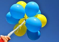 Bos van de gele en blauwe ballons in de menselijke hand Royalty-vrije Stock Foto's