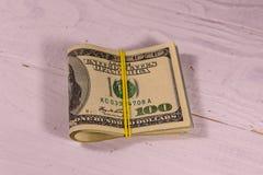 Bos van de honderd dollarsrekeningen met rubber op houten lijst stock foto's
