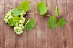 Bos van druiven en wijnstok op houten lijst Stock Afbeelding