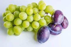 Bos van druiven met pruimen op witte lijst stock foto