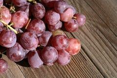 Bos van druiven op een houten lijst oud, buitenhuis royalty-vrije stock afbeeldingen