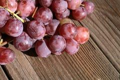 Bos van druiven op een houten lijst oud, buitenhuis stock fotografie