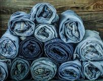 Bos van jeans op een houten achtergrond, modieuze kleren worden verdraaid die royalty-vrije stock afbeeldingen