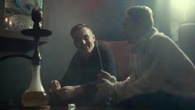 Bos van jonge kerels die en waterpijp in langzame motie roken lachen stock video