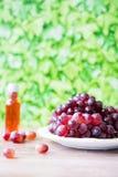 Bos van rode druiven en wijn tegen groene onduidelijk beeldachtergrond royalty-vrije stock afbeelding