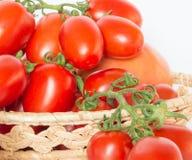 Bos van tomaten in een mand met tomatesap Royalty-vrije Stock Foto's