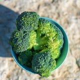 Bos van verse groene broccoli in kom op rustieke openluchtachtergrond van een steenlijst Hoogste mening royalty-vrije stock fotografie