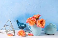 Bos van verse oranje rozen in kop tegen blauwe muur Royalty-vrije Stock Foto's