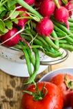 Bos van verse organische slabonen, rode radijs in metaalvergiet, rijpe tomaten op houten keukenlijst, gezonde voeding, het schone Royalty-vrije Stock Foto's