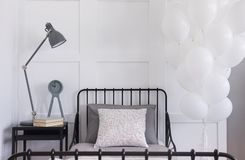 Bos van witte ballons naast enig zwart metaalbed met grijs beddegoed en gevormd hoofdkussen, echte foto met exemplaarruimte op stock foto