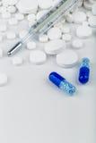 Bos van witte tabletten met blauwe pillen en thermometer Royalty-vrije Stock Afbeelding