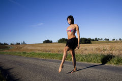 Bosa brunetka krzyżuje wiejską drogę obrazy stock