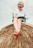 Bosa chłopiec czyta książkę siedzi na wierzchołku haystack Zdjęcia Royalty Free