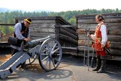 Bosatt historia turnerar, med handböcker som avfyrar en kanon, fortet William Henry, sjön George, New York, 2015 royaltyfri foto