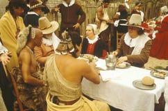Bosatt historiereenactment av Pilgrims och indier som äter middag på den Plymouth kolonin, Plymouth, MOR Royaltyfri Bild