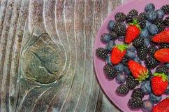 Bosbessen en aardbeien op een roze plaat Stock Foto's