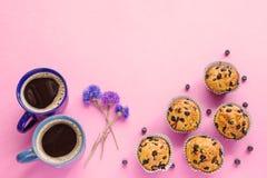 Bosbessenmuffins, twee koppen van koffie en korenbloemen op roze bedelaars Stock Foto's