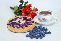 Bosbessenpastei, kop thee, hoop van bosbessen en rode rozen op een witte achtergrond - stillevenvoedsel Royalty-vrije Stock Foto's
