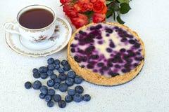 Bosbessenpastei, kop thee, hoop van bosbessen en rode rozen op een witte achtergrond - stillevenvoedsel Stock Foto