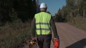 Bosbouwarbeider die op de weg met kettingzaag lopen stock video