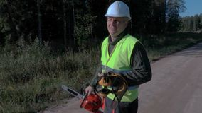 Bosbouwarbeider op de weg met dichtbij gebroken en gevallen kettingzaag net stock videobeelden