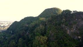 Bosbouwheuvel met tempel door stad onder heldere duidelijke hemel stock videobeelden