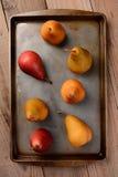 Bosc и красные груши на листе выпечки на деревянной таблице Стоковое Изображение RF