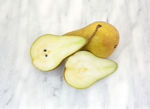 Bosc pears on marble cutting board Royalty Free Stock Images