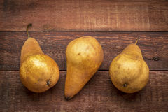 Bosc pears on rustic wood Stock Photo