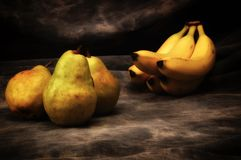 Bosc pears and yellow bananas on gray studio backdrop royalty free stock image