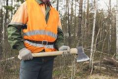 Boscaiolo con un'ascia sui precedenti della foresta Immagine Stock