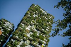 Bosco Verticale, vertical forest apartment buildings and poplar branches in the business district of Porta Garibaldi, warm toned. Milan, Italy, October 9, 2017 royalty free stock photos