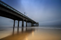 Boscombe Pier at Dawn. Early morning light reflects on golden sands at Boscombe Pier near Bournemouth in Dorset Royalty Free Stock Images