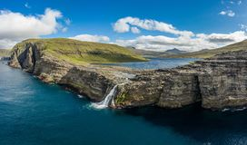 Bosdalafossur waterfall on Vagar island coastline aerial view