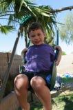 Bose młode chłopiec huśtawki w swingset Obraz Stock