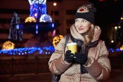 Boshaftes blondes Mädchen, das auf Hintergrund mit Lichtern auf Th steht Lizenzfreies Stockfoto