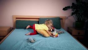 Boshaftes Kinderwerfende Spielwaren auf Bett im Schlafzimmer stock footage
