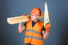 Boskennisconcept De mens, manusje van alles in helm, bouwvakker houdt handsaw en houten stralen, grijze achtergrond timmerman royalty-vrije stock afbeeldingen