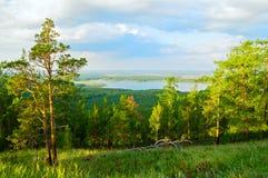 Boslandschap met bomen, berghellingen en meer onder zacht zonsonderganglicht stock foto