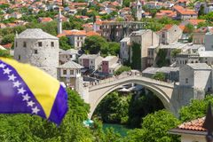 Bosnia and Herzegovina. Flag in Mostar overlooking Stari Most Old Bridge royalty free stock image