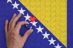 Bosnia and Herzegovina flag is depicted on a puzzle, which the man`s hand completes to fold.  vector illustration
