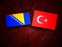 Bosnia and Herzegovina flag with Turkish flag on a tree stump  Royalty Free Stock Photos
