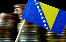 Bosnia and Herzegovina flag waving with stack of money coins Stock Photo