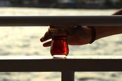 从bosphorus的饮用的土耳其茶在伊斯坦布尔 免版税库存图片