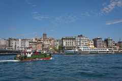 Bosphorus Activity with Galata Neighborhood in the Background. ISTANBUL, TURKEY – APRIL 27: Boat activity on the with the Galata Tower and neighborhood behind Royalty Free Stock Photography