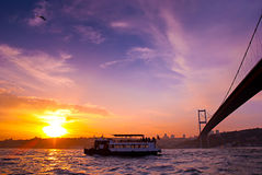Bosphorus Bridge and excursion boat at sunset, Istanbul, Turkey Royalty Free Stock Photos