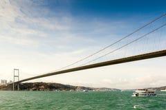 Bosphorus bridge, Istanbul, Turkey. View to Bosphorus bridge from the strait with floating boat, Istanbul, Turkey Stock Photo