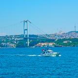 The Bosphorus Bridge and motorboat. The Bosphorus Bridge 15 July Martyrs Bridge and motorboat in Istanbul, Turkey stock images